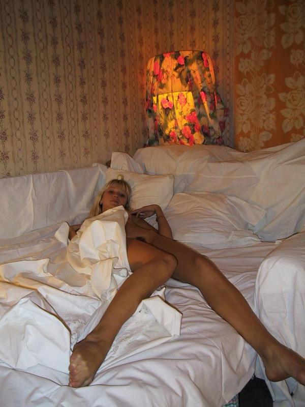 Милая блондинка раздевается и валяется на постели голышом - секс порно фото